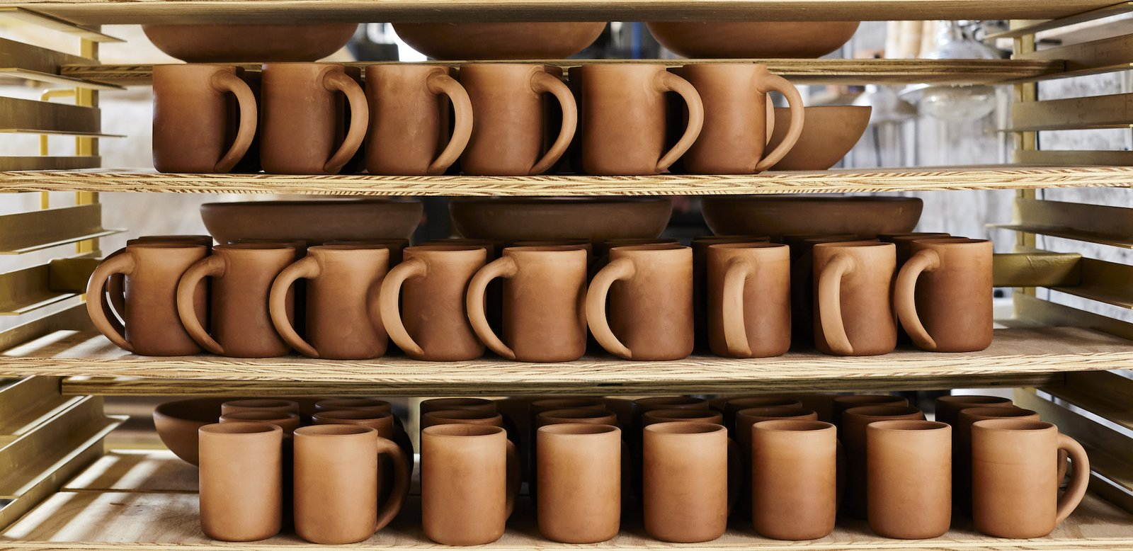 Stacks on stacks of East Fork Pottery's The Mug waiting to be glazed