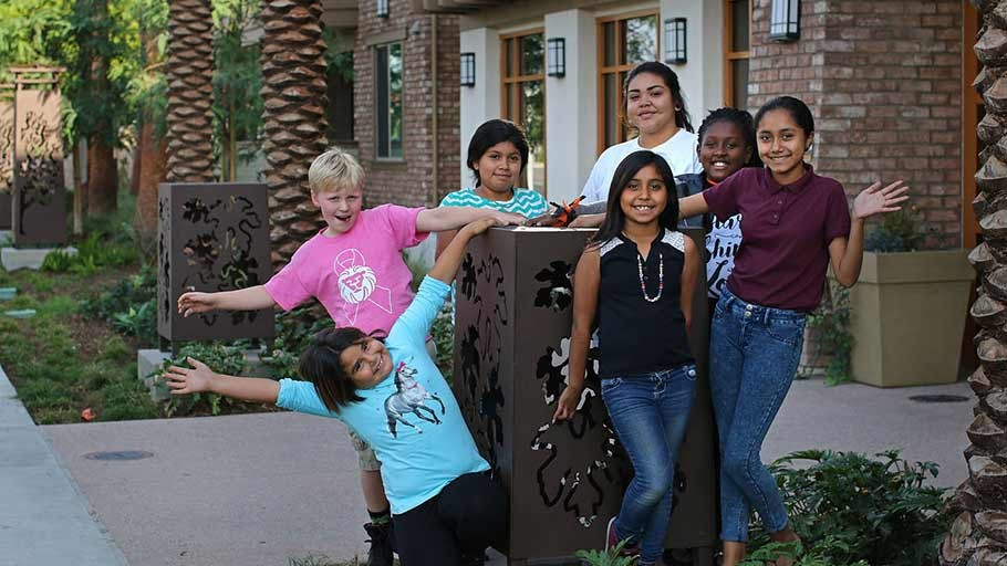 Happy children who live at Rockwood in Anaheim, CA stand around monument sign