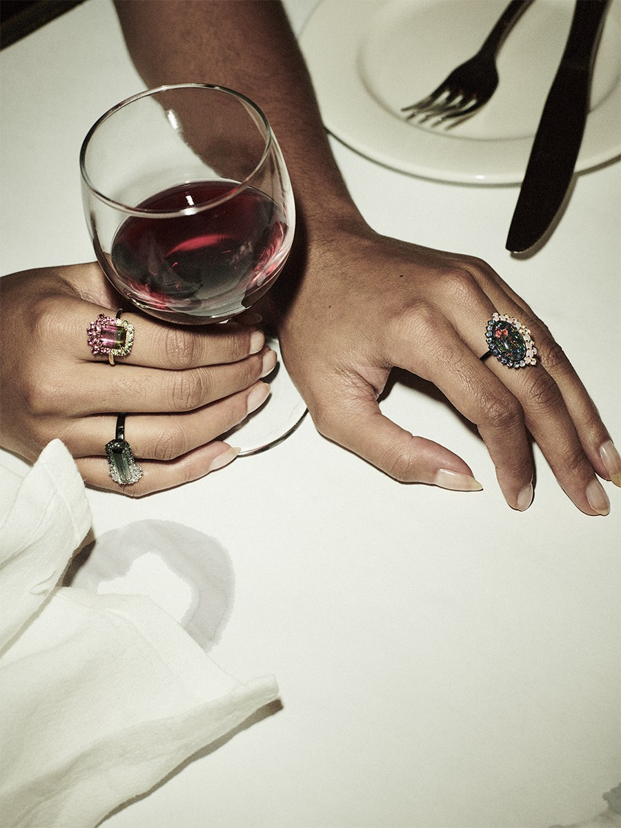 a womans hands rest on a white table cloth holding a glass of red wine wearing rings by carla maxine