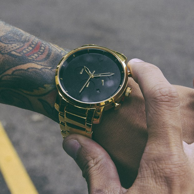 black and gold link watch on a mans wrist