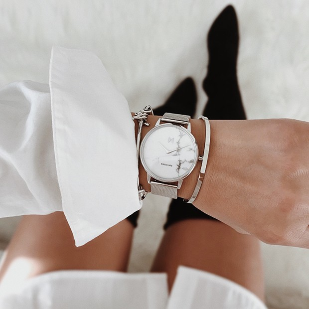 silver stainless steel watch with a white marble face on a womans wrist