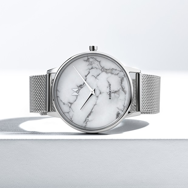 silver stainless steel watch with a white marble face on a white surface
