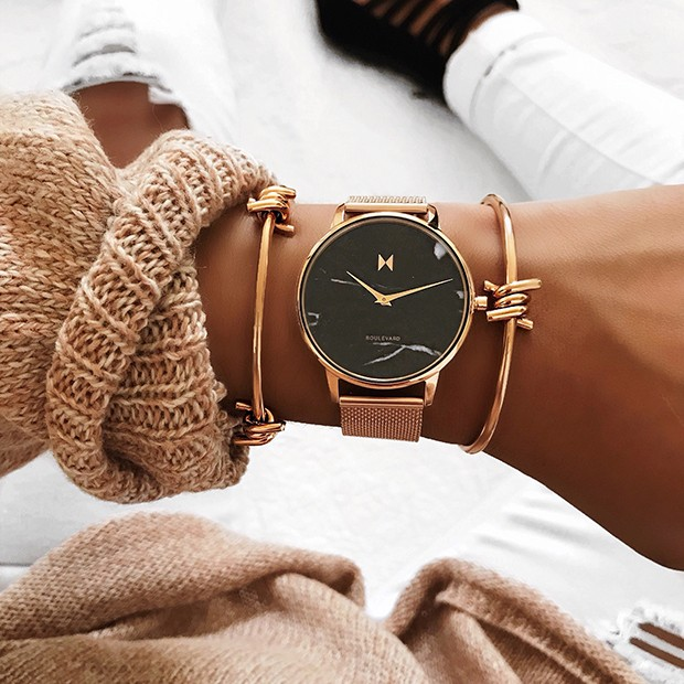 black marble and rose gold stainless steel watch on a womans wrist