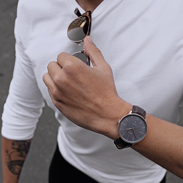 grey, rose gold and brown leather watch on a mans wrist