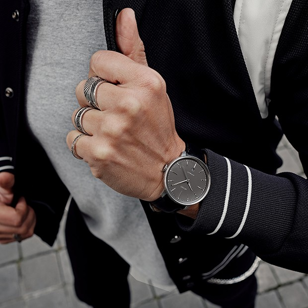 silver and black leather watch on a mens wrist