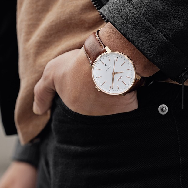 white, rose gold and brown leather watch on a mans wrist