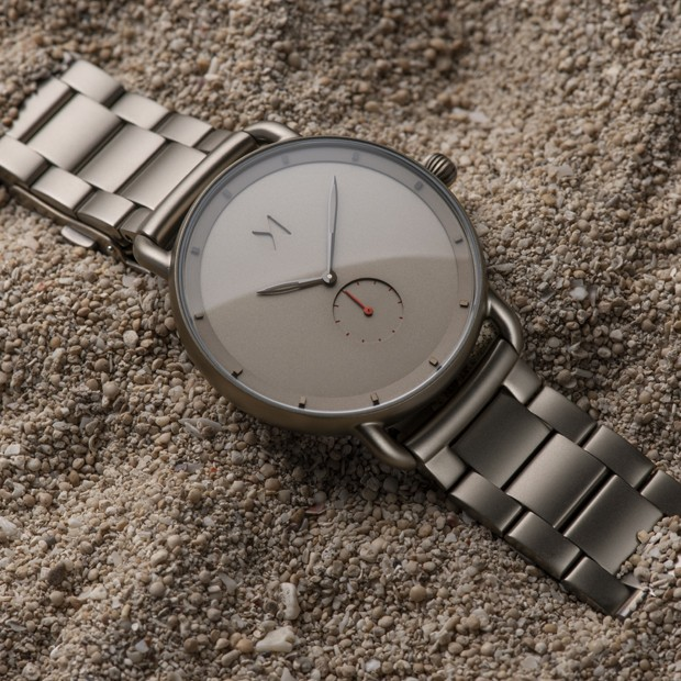 taupe stainless steel watch on a flat surface