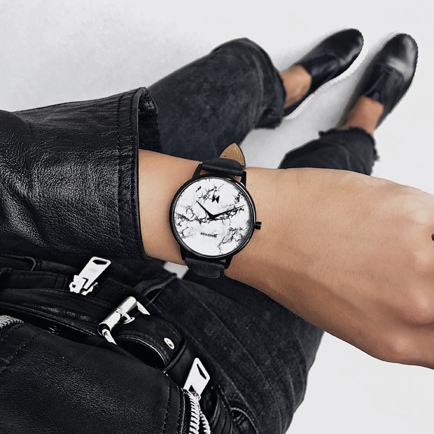 white marble and black leather watch on a womans wrist