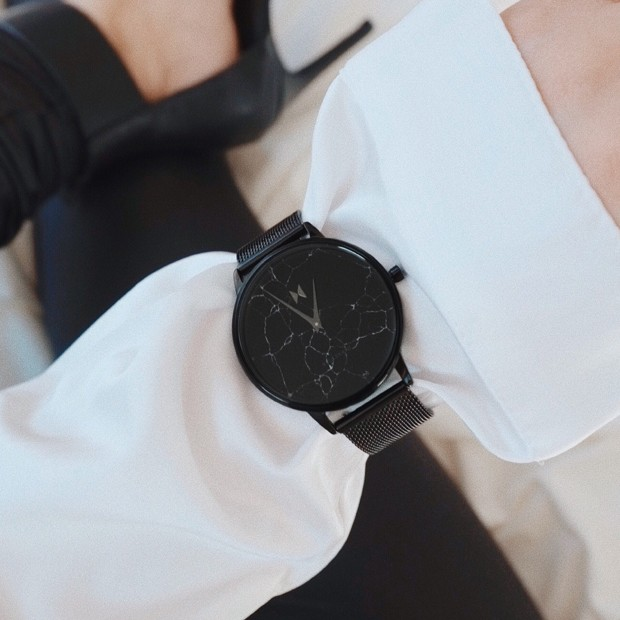 all black stainless steel watch with marble face on a womans wrist