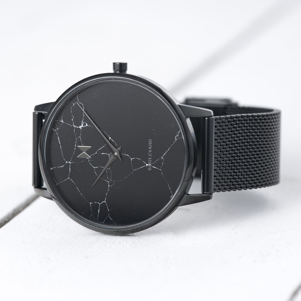 all black stainless steel watch with marble face on a white surface