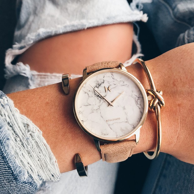 gold and beige leather watch with a marble face on a womans wrist