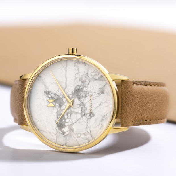 gold and beige leather watch with a marble face on a white surface