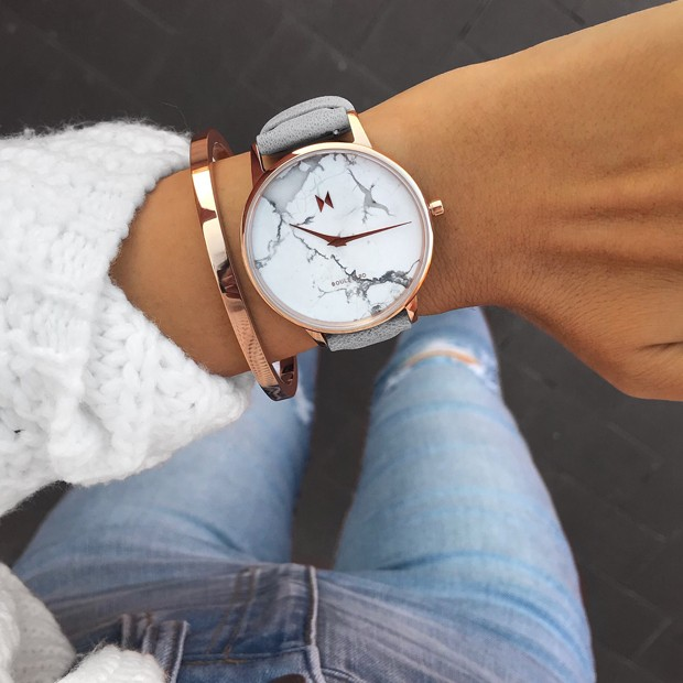 white marble, rose gold and light grey leather watch on a womans wrist