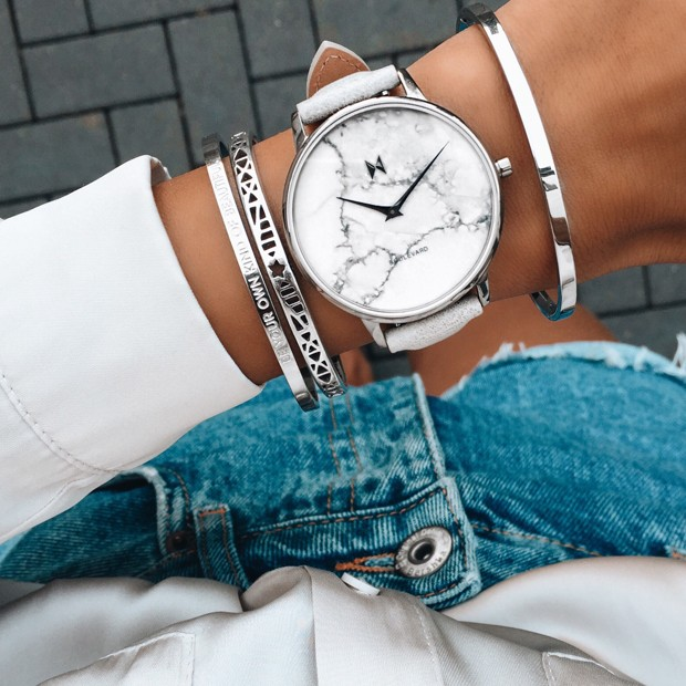 white marble, gunmetal and grey leather watch on a womans wrist