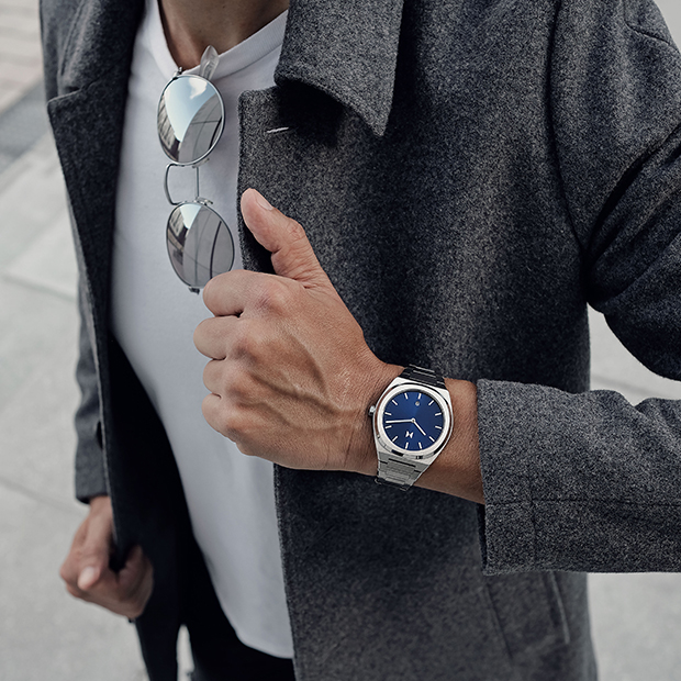 blue and silver link watch on a mans wrist