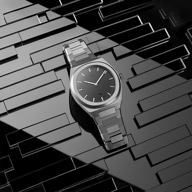 grey and silver link watch on a dark background