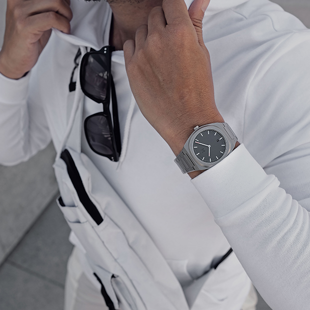 grey and silver link watch on a mans wrist
