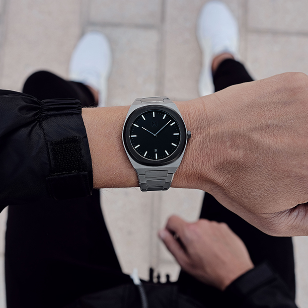 black and silver link watch on a mans wrist