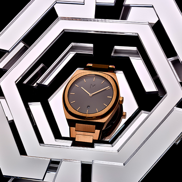 black and bronze link watch on a silver surface