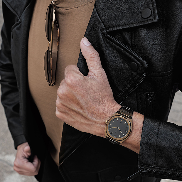 black and bronze link watch on a mans wrist