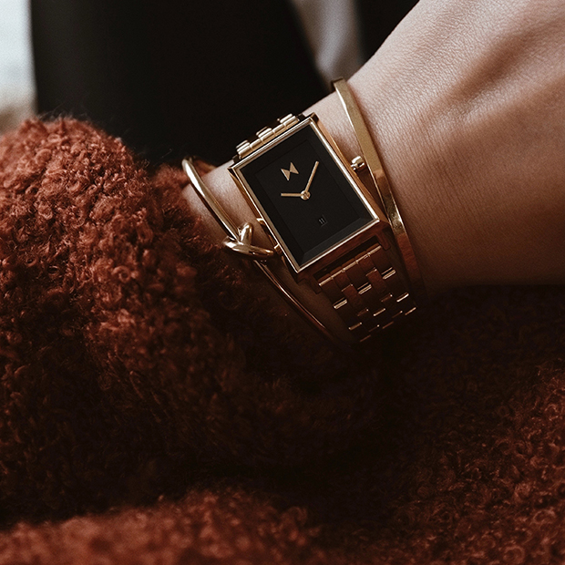 black and gold link square watch on a womans wrist