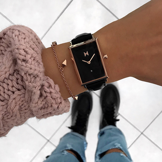 black and rose gold watch on a womans wrist