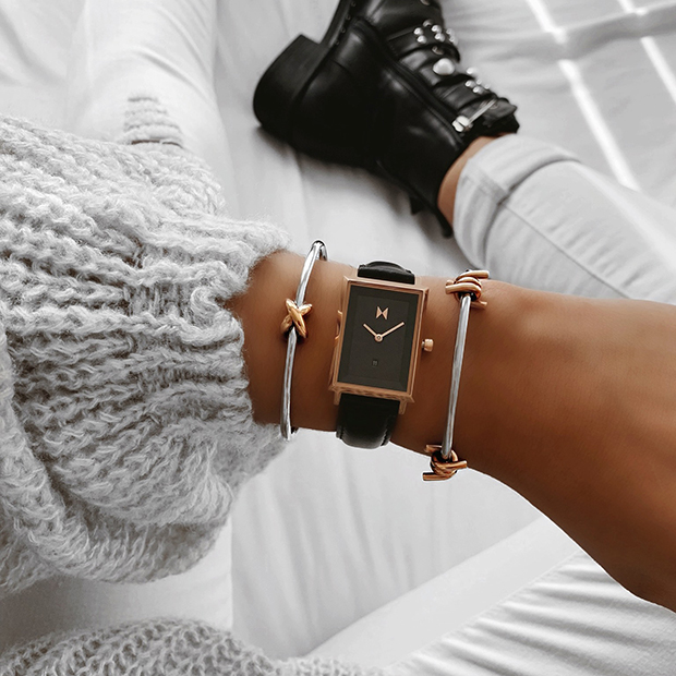 rose gold and black leather watch on a womans wrist