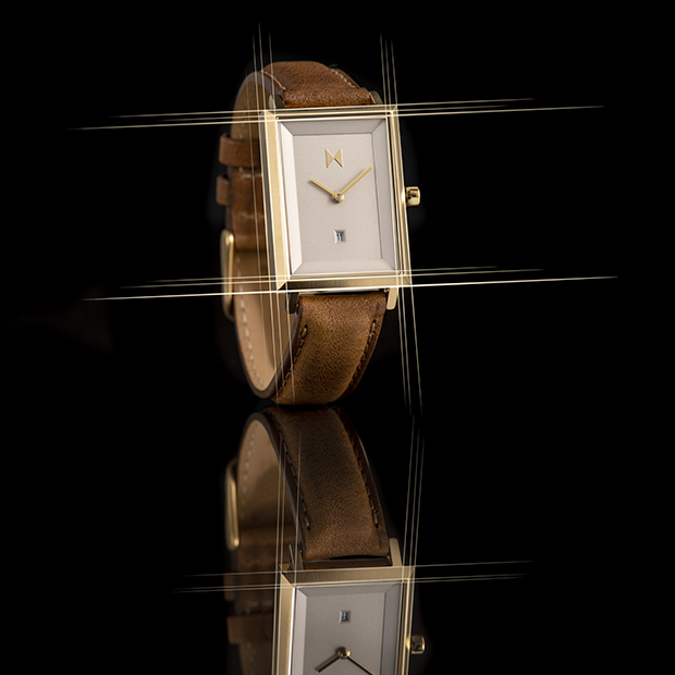 gold and brown leather watch on a black background