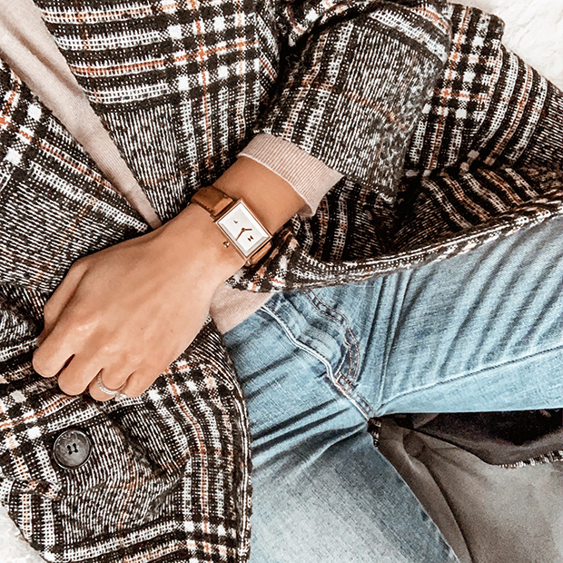 gold and brown leather watch on a womans wrist