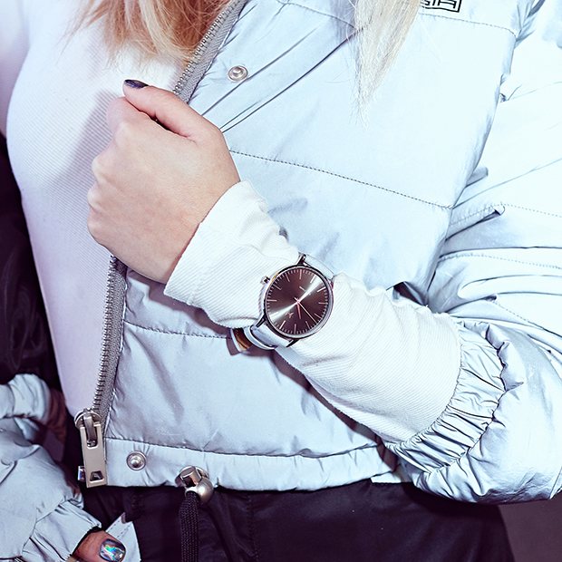 silver and grey leather watch on a woman's wrist