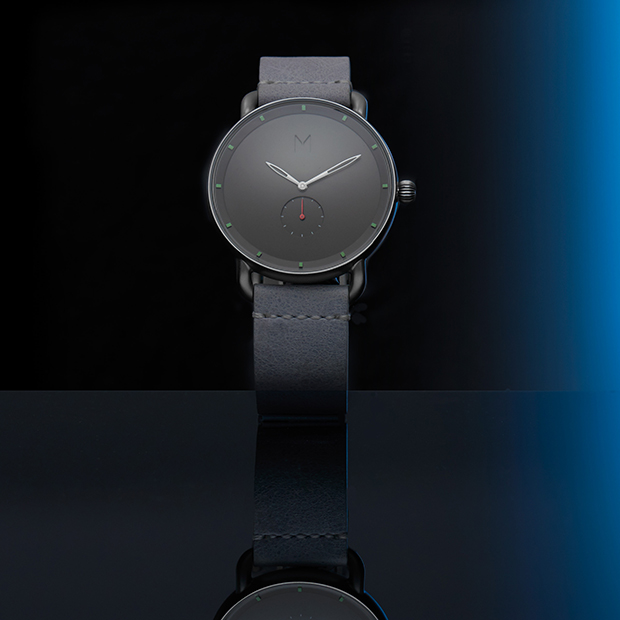 silver and grey watch on a black and blue background