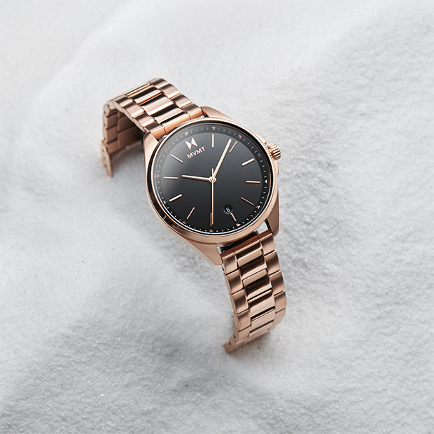 Rose gold and black women's watch on background