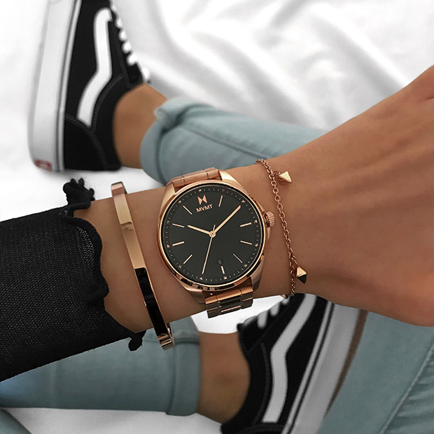 Rose gold and black women's watch on wrist
