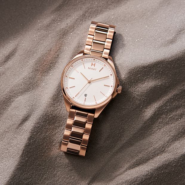 white and rose gold watch laying on sand