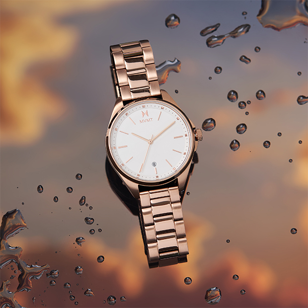 white and rose gold watch on a colored background