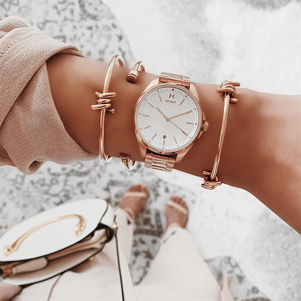 white and rose gold watch on a woman's wrist