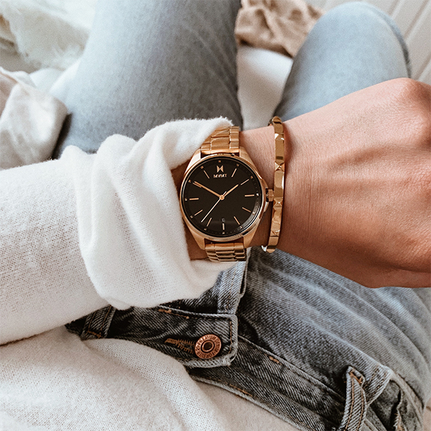 gold and black watch on woman's wrist