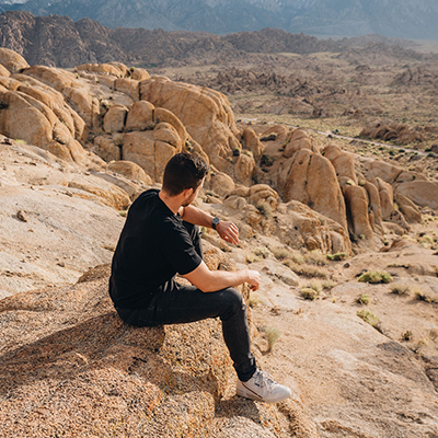 man sitting on rock with watch on