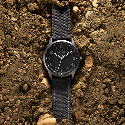 Silver and grey nylon watch on a dirt surface
