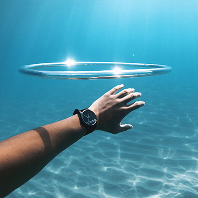 Silver and grey nylon watch on a mans wrist under water