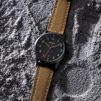 Black and tan nylon watch laying in sand