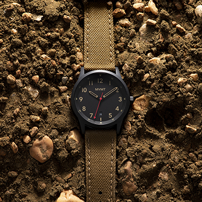 Black and tan nylon watch on a dirt surface