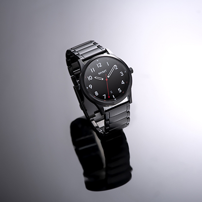 Black stainless steel watch on a grey background