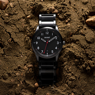 Black stainless steel watch on a dirt surface