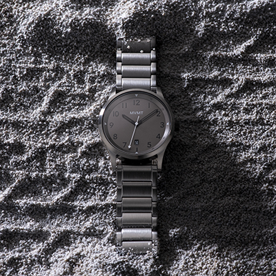 Gunmetal stainless steel watch in the sand
