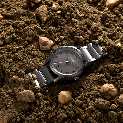 Gunmetal stainless steel watch on a dirt surface