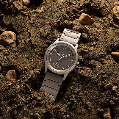 Taupe stainless steel watch on a dirt surface