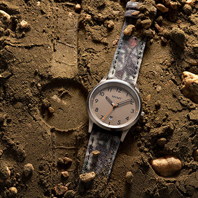 Taupe and camouflage nylon watch on a dirt surface