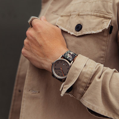 Taupe and camouflage nylon watch on a mans wrist