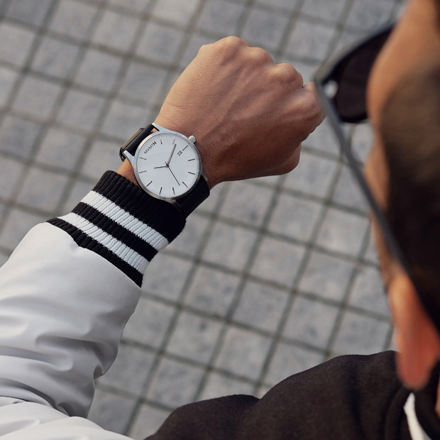 white and black leather watch on a mans wrist